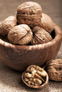 Walnuts in a wooden bowl and one cracked walnut Royalty Free Stock Image