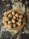 Walnuts in a wooden bowl on wooden rustic background, top view Royalty Free Stock Photo