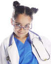 Wanna be doctor closeup image of a young elementary girl smiling over her glasses and wearing scrubs a lab coat and stethoscope Stock Image
