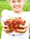 Want strawberries young girl gives viewer a quart of Royalty Free Stock Photo