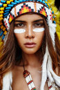 War bonnet portrait female model with red skin dressed in tribal from feathers and traditional makeup Stock Photos