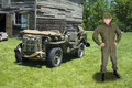War military army officer and retro jeep vehicle a wearing combat fatigues is standing in the field in front of a the leader is Royalty Free Stock Photos