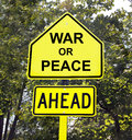 War or peace ahead sign yellow with black letters of with trees in the background Royalty Free Stock Image