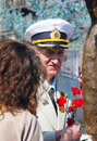 War veteran recieves flowers a woman gives red carnation to a victory day celebration on may in moscow Stock Photo