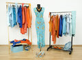 Wardrobe with complementary colors orange and blue clothes arranged on hangers dressing closet shoes accessories a dress a Stock Photo