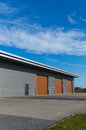 Warehouse with brown door new storage doors and blue sky Stock Image