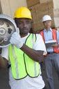Warehouse den bärande cylindern för arbetaren med chefen i bakgrund Arkivbild