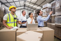 Warehouse manager pointing something to his colleagues in a large Royalty Free Stock Photo