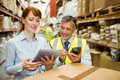 Warehouse managers looking at tablet pc in a large Stock Photo