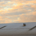 Warehouse roof with ventilation at sunset cloudy background Stock Image