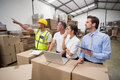 Warehouse worker pointing something to his colleagues in a large Stock Images