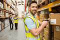 Warehouse worker scanning box while smiling at camera Royalty Free Stock Photo