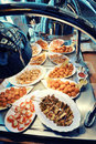 Warm buffet with an assortment of dishes under lights array platters container sliced meat fish fishcakes and meatballs at a Stock Photo