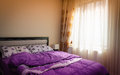 Warm and cozy bedroom modest interior with soft sun light coming from the windows Royalty Free Stock Images