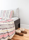 Warm cozy slippers near bed a with striped linen Royalty Free Stock Photos