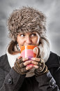 Warm drink woman in winter clothes drinking a hot beverage from a mug Stock Photo