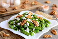 Warm green beans salad with cottage cheese and walnuts on a white plate and old wooden table. Rustic style. Easy green beans