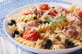 Warm salad fusilli pasta, tuna and tomatoes close up. horizontal Royalty Free Stock Photo