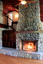Warm scene in lit stone fireplace showcasing craftsmanship in rustic home Royalty Free Stock Photo