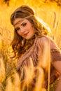 Warm summer haze seventies hippie girl in grainfield. Royalty Free Stock Photo