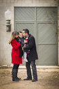 Warmly dressed family loving son in front of rustic building young mixed race couple winter clothing hugging and kissing together Royalty Free Stock Photo