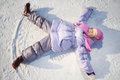 Warmly dressed little girl in pink scarf and hat lies with outstretched arms legs on snow winter Stock Photography