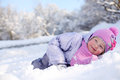 Warmly dressed little happy girl in pink scarf and hat lies on snow looks up at winter day Stock Photography