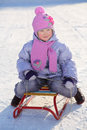 Warmly dressed smiling girl in pink scarf and hat sleds on snow winter Stock Photo