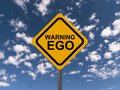 Warning ego yellow traffic sign with black text against blue sky with clouds Stock Photography