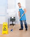 Warning notice as a janitor mops the floor yellow to caution people to slippery wet surface in an office building Royalty Free Stock Photo