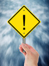 Warning road sign with an exclamation mark hand holding Stock Image