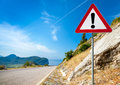 Warning road sign with an exclamation mark in red triangle on mountain highway Stock Image