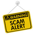 Warning of scam alert a yellow and black sign with the words isolated on a white background Royalty Free Stock Image