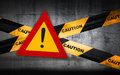 Warning sign with exclamation mark on striped caution tape Royalty Free Stock Image
