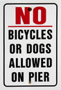 Warning sign prohibiting bicycles or dogs on pier Royalty Free Stock Photography