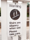A warning sign saying stairs are slippery when wet please take c