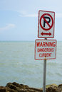 Warning signs on florida coast two cliff top one with uppercase letter p and diagonal red line through it indicating no parking to Royalty Free Stock Photo