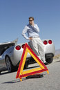 Warning triangle with man on call by car on road closeup of in front of a an empty Stock Image