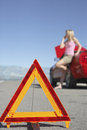 Warning triangle with woman on call by car on road closeup of in front of a blurred red an empty Stock Image