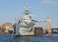 Warship hms belfast which is now used as a museum on the river thames with the landmark of tower bridge in the background Royalty Free Stock Photo