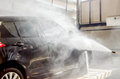 Washing black car by pressure washer gun in car wash shop Stock Image