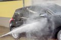 Washing black car by pressure washer gun in car wash shop Stock Images