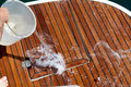 Washing the deck with water throwed from a plastic buket Royalty Free Stock Images