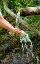 Washing hands by spring water under wooden gutter over green natural background Stock Photography