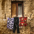 Washing hangs on a line in front of a half shuttered window in a brick wall of a Tuscan village in a square format. Royalty Free Stock Photo