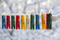 Washing line row colorful pegs covered snow queued row Royalty Free Stock Photos