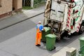 The waste paper collector uploads green containers in a truck prepares to unload germany Royalty Free Stock Photos
