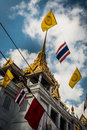 Wat traimitr withayaram the golden buddha temple bangkok with flgs of thailand and thai buddhist dharmacakra flag in foreground Royalty Free Stock Images