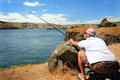Watch my pole man fishing for sturgeon on the columbia river in eastern washington with view of territory under clear blue skies Stock Photo