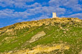 Watch tower on a hilltop stone built perched upon rocky hill top approached by grassy slopes and with bright blue cloudy sky Royalty Free Stock Photos